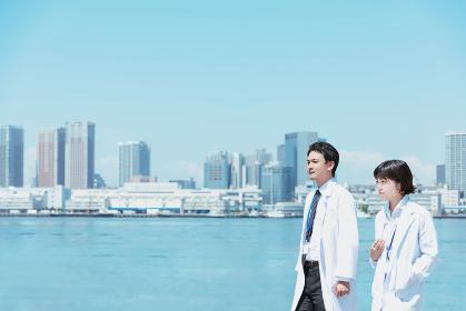 会話しながら海辺を歩く白衣の男女