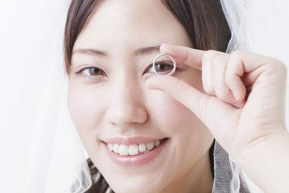 結婚指輪を持って微笑む花嫁