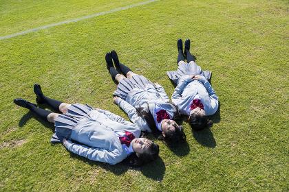 芝生に寝転ぶ高校生