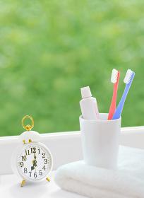 窓辺の歯ブラシと時計とタオル