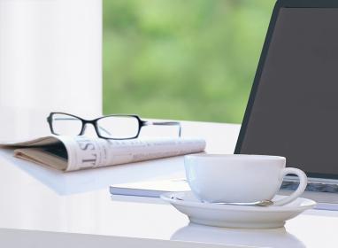 パソコンとコーヒーカップと新聞