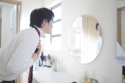 鏡の前でネクタイを締める男性