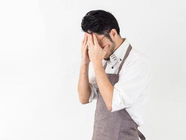 家事に失敗・反省・困惑している男性のイメージ