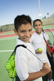 Young boy and girl with tennis equipment on tennis court focus on boy portrait
