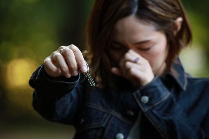 泣きながら鍵を渡す女性