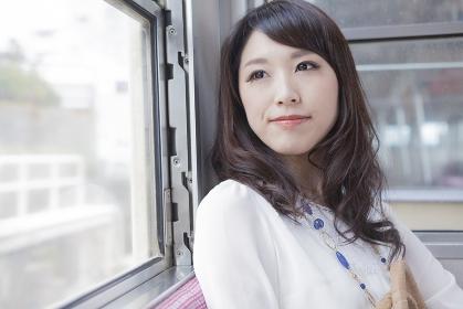 電車の窓から景色を眺める女性