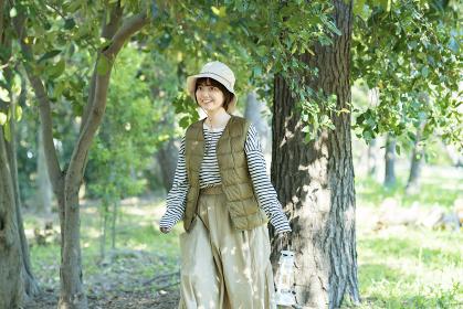 明るい森を散策する若い女性