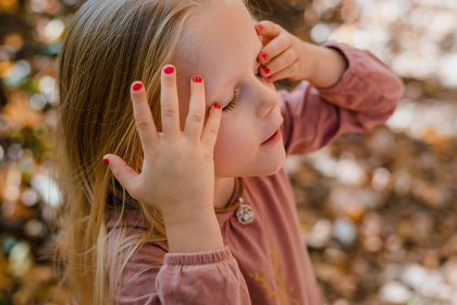 Little girl with nail polish pushing hair out of face