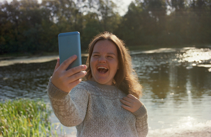 Diabetic woman making selfie on smartphone in autumn near the river.