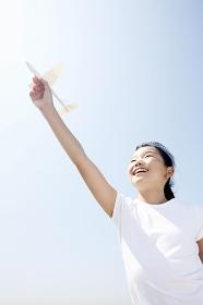 紙飛行機を飛ばそうとする少女