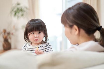 ママとおやつを食べるアジア人の子供