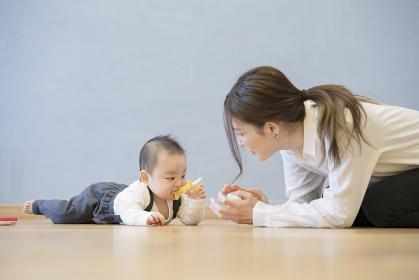 室内で、赤ちゃんと遊ぶお母さん