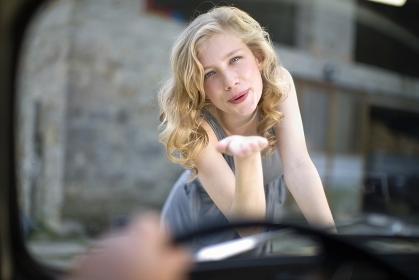車内の男性に投げキスをする女性