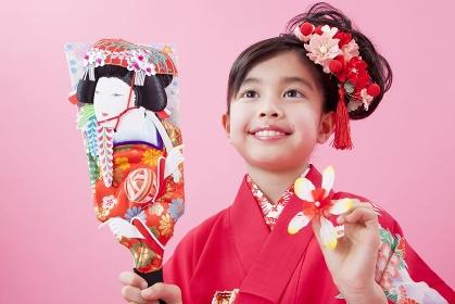 羽子板を持って微笑む女児