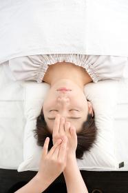 鍼灸院で眉間の指圧を受ける女性