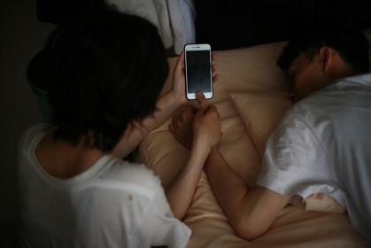 寝ている男性の指でスマートフォンの指紋認証を解除する女性
