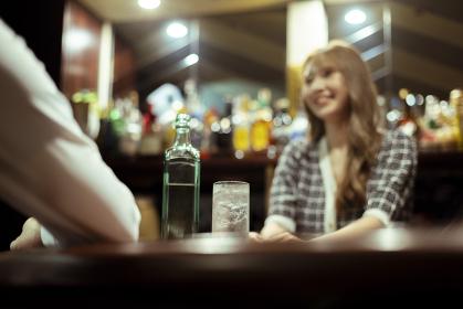 カウンターバーでお酒を提供する若い女性