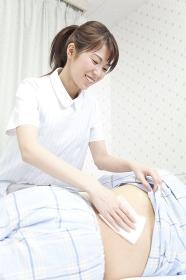 患者の体を拭く看護師
