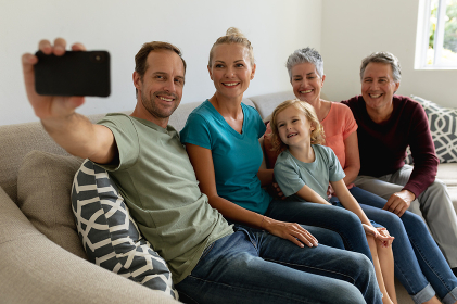 Caucasian father sitting on couch with his wife, parents and son, smiling and taking selfie. happy three generation family spending time together at home.