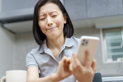 ストレスを抱えた表情でスマホを見る女性