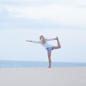 Free woman streching on beach at down.
