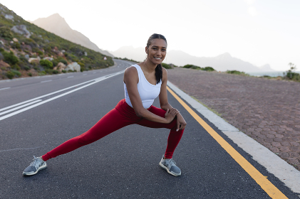 Fit african american woman in sportswear stretching on a coastal road. looking at the camera and smiling. healthy lifestyle, exercising in nature.