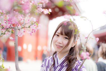 桜の前でほほ笑む袴の女性