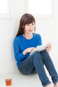 部屋でタブレットコンピューターを見る女性