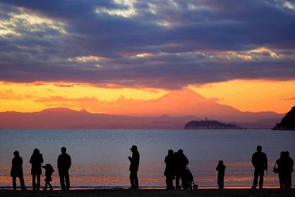 海岸から富士山が見える夕景を眺める人々のシルエット