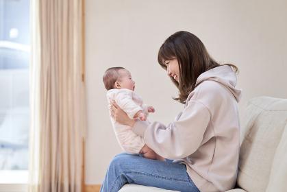赤ちゃんを笑わせるアジア人のお母さん