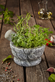 Fragrant herbs in mortar on wooden table with condiments and oil