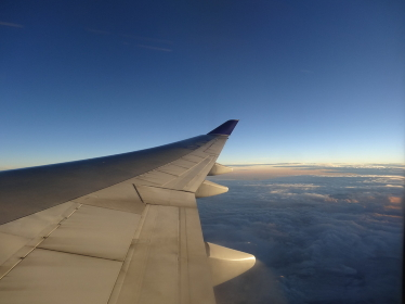 飛行機の翼と空(雲、オレンジがかった空、晴れ)