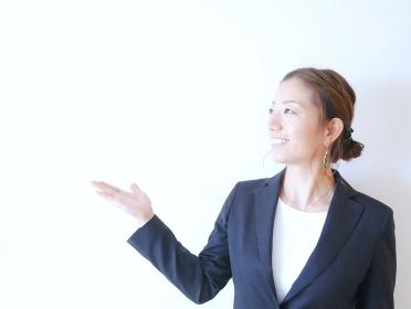 スーツを着て手を挙げている女性