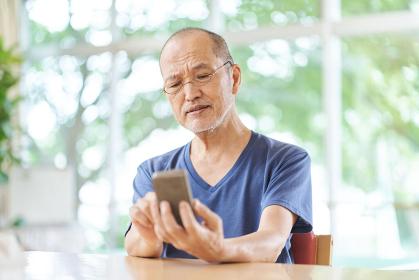 老眼でスマートフォンが見えづらい高齢者