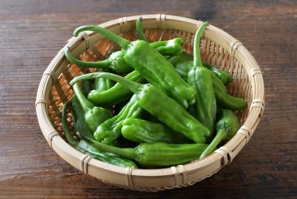木目板背景の緑の夏野菜のししとう