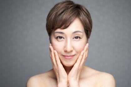 両手で頬の潤いを確かめる中年の日本人女性