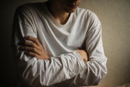 腕を組む男性