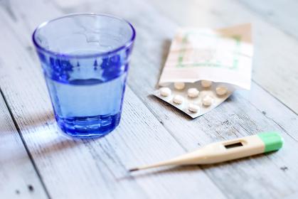 体温計と薬、ガラスコップと水、ヘルスケア医療イメージ