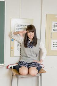 学校の自習室の机で敬礼する女子高生