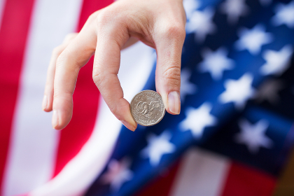 close up of hands with coins over american flag