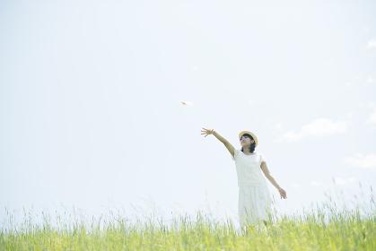 草原で紙飛行機を飛ばす女性