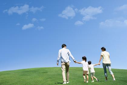 芝生と手を繋ぐ家族