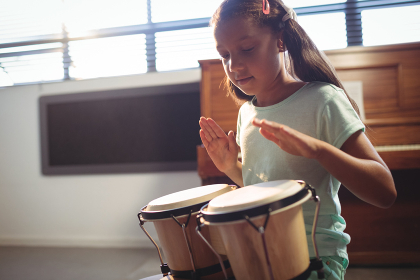 Girl playing bongo drums in classroom