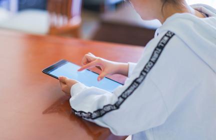 リビングでタブレット端末でゲームをする若い女性