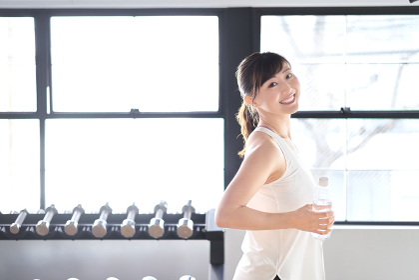 笑顔でダンベルトレーニングをするアジア人女性