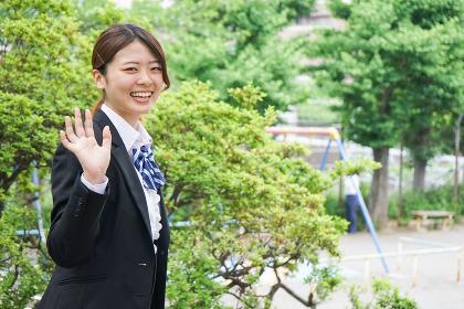 笑顔で手を振る制服姿の学生