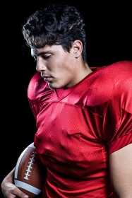 American football player holding ball while eyes closed