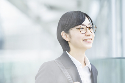 スーツ姿で笑顔を見せる若い女性