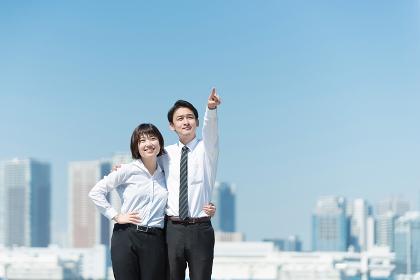 肩を組んで指をさす男女(ビジネスイメージ・目標)