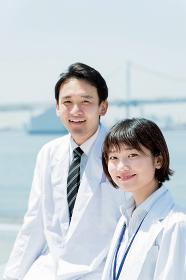 カメラ目線の白衣の男女(医者・医療従事者のイメージ)